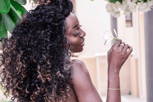 woman-holding-white-plumeria-flower